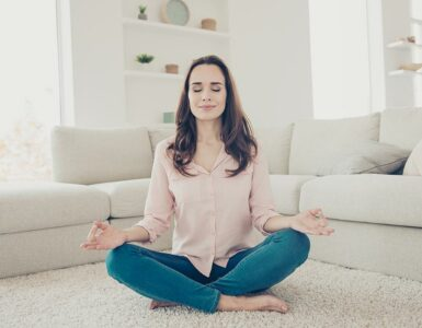 woman meditating at home in her living room